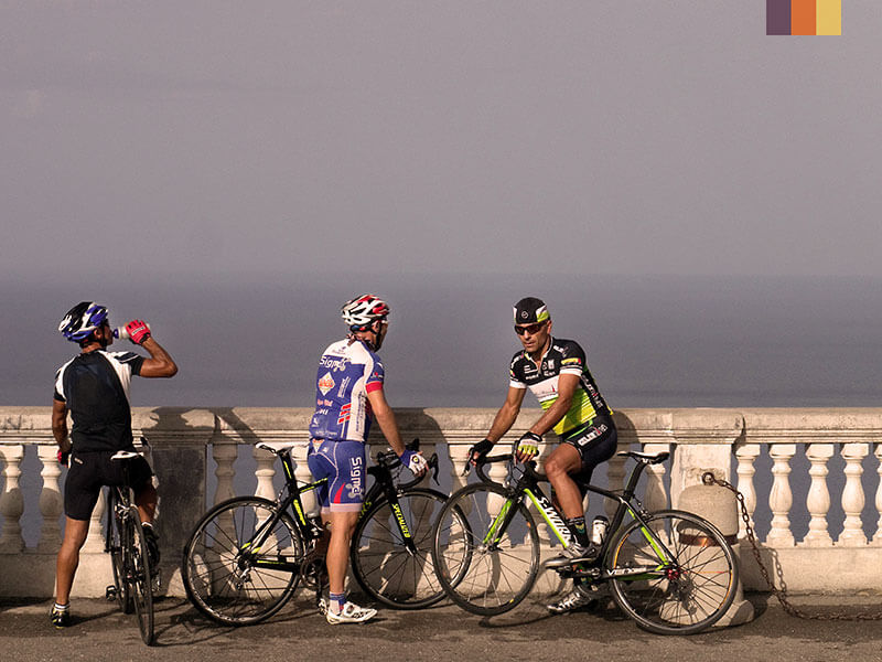 Three cyclists looking at the ocean on a cycling holiday in Sicily