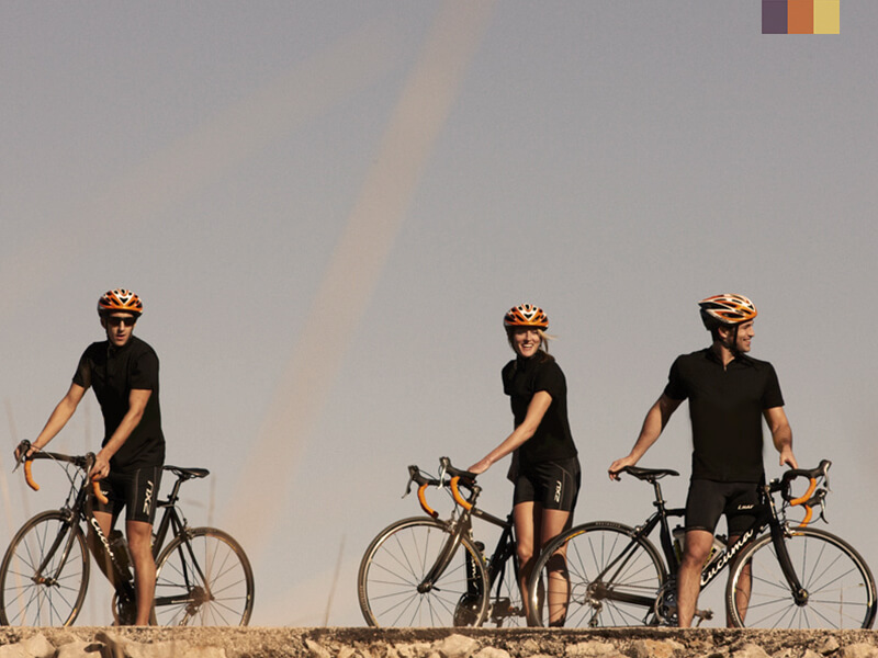 A group of cyclists taking a break and laughing on their cycling holiday in Port Pollensa