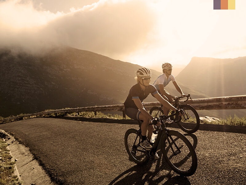 Two cyclists on a road in Tenerife with mountains in the background