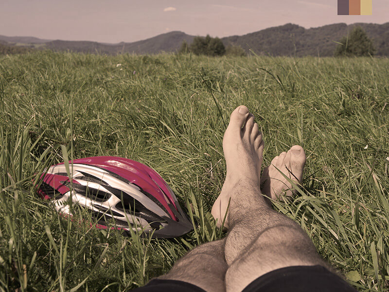 A cyclists relaxing in a field on their Tuscany cycling holiday