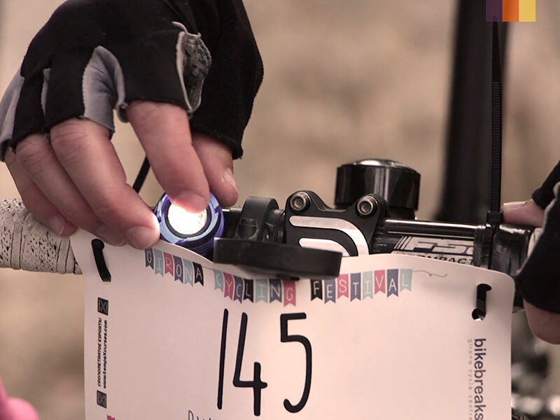 A cyclist attaching his race number to his handleabrs at the Girona Festival of Cycling
