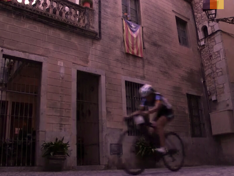 A female cyclist riding  through Girona during the Nocturne at the Girona granfondo