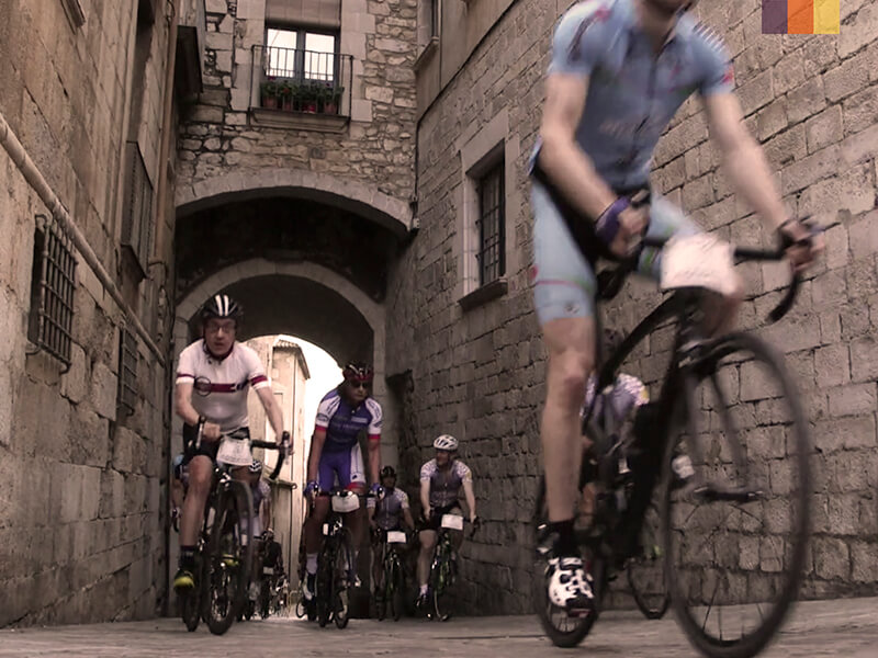 A group of cyclists riding through Girona during the Nocturne at the Girona granfondo